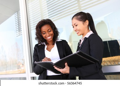 Two interracial (african and asian) business women team at office building