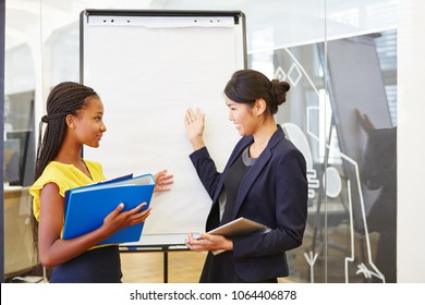 Two interracial business women in business presentation with whiteboard