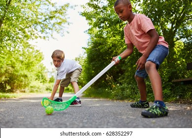 Two interraciat children playing street hockey as team and friends