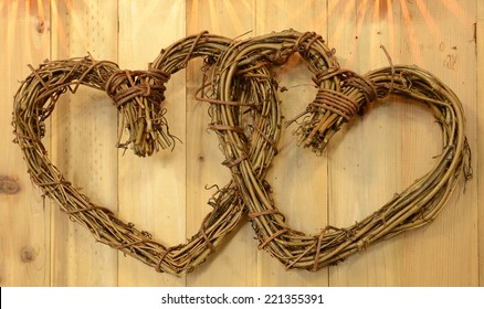 Two intertwined wicker hearts on a wooden background for Valentines Day