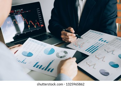 Two investors are working together with analyzing the stock data graphs in the paper and viewing the data on the laptop screen.