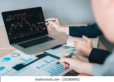 Two investors working together are analyzing the stock chart on the computer screen at the company.