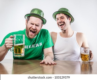 Two Irish friends getting drunk on Saint Patrick's Day in bar together laughing cracking up over beer