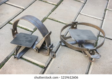 Two iron rusty traps lie on the stone floor, not cocked and cocked