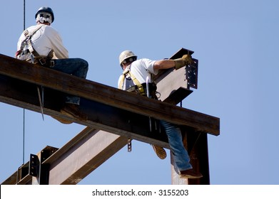 Two ironworkers atop the skeleton of a modern building. One man is positioning a very large beam while the other watches.
