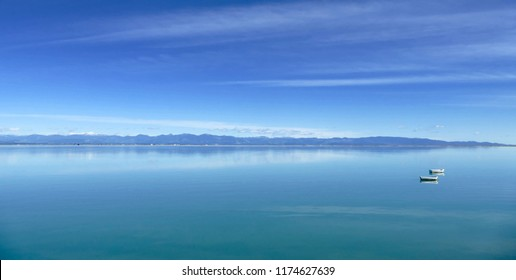 Two Isolated Boats on Blue Lake beneath Blue Sky in Nelson, New Zealand