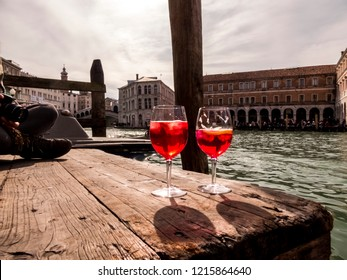 Two isolated glass of red drink called Spritz on wood wharf in canal grande of Venice old palace on background.