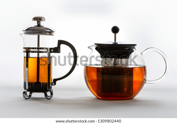 Two isolated glass tea pots of different shapers: french press and a round pot with tea on a white background