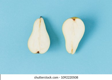 Two isolated pear halves shot from above on a pastel blue background.