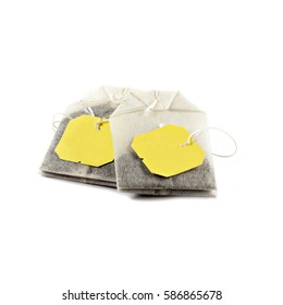 Two isolated tea bags with yellow tags on a pure white background