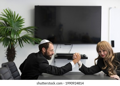 Two Israeli business partners Competing In Arm Wrestling in office. Jewish man in yarmulke and woman with blond hair, tense faces compete armwrestling. Equal rights. Feminism, Gender equality concept