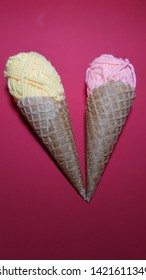 Two Italian style waffler cones and yellow and pink balls of wool representing ice cream on a background.