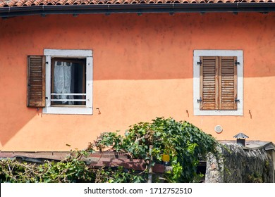 Two Italian windows on the red wall facade with open and closed brown color classic shutters