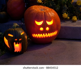 Two jack-o-lanterns are glowing from candles inside, on the front porch, ready for Halloween