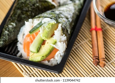 Two Japanese Temaki hand roll sushi with raw salmon, avocado and cucumber in take away delivery tray with soy sauce