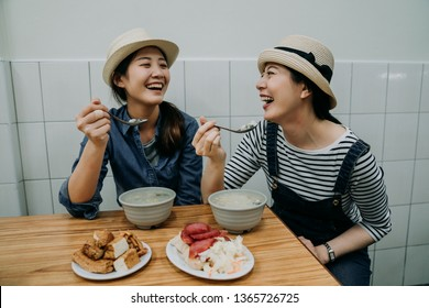 two japanese traveler in taiwan trying taiwanese local food. chinese lady spoon eating congee porridge stinky tofu sausage and korean cabbage in vendor store. smiling girls in traditional restaurant
