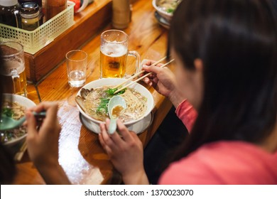 Two Japanese women friends eat ramen at local restaurant during quiet lunch
