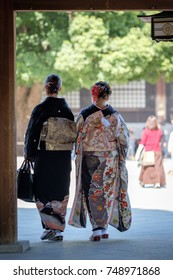 Two Japanese women (mother and daughter) wearing sophisticated Kimono in a shrine in Tokyo on a sunny day in Autumn.