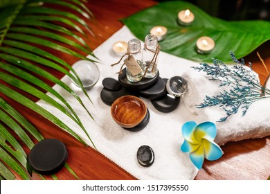 Two jars of aromatic oils standing on stones for a therapy stone and located on a terry towel next to which a flower lies, there are transparent spheres, a twisted towel and a sprig of lavender
