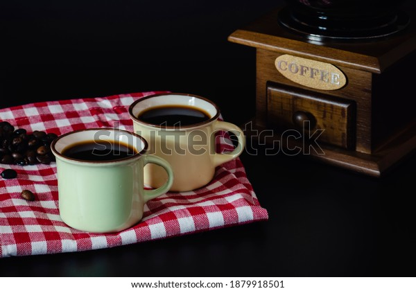 Two jars of coffee and coffee beans on a red and white tablecloth, a coffee grinder on a black background