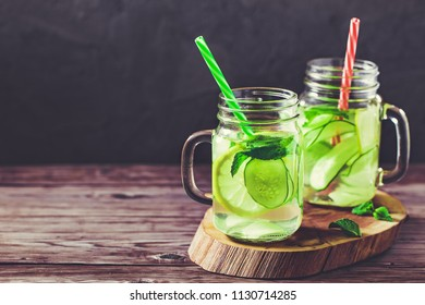 Two jars of fresh water infused with cucumber, lemon, ginger and mint.