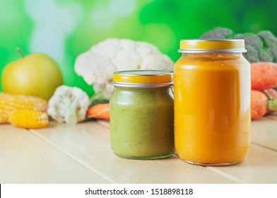 Two jars with vegetable puree on the light wooden background. Selective focus.
