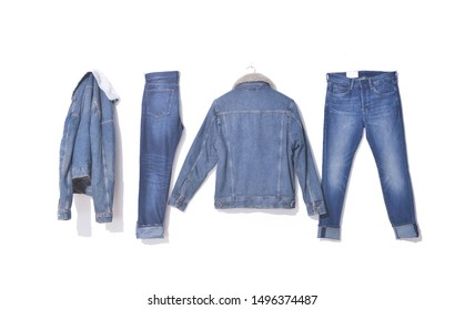 two jeans denim jacket on hanging and two blue jeans-white background