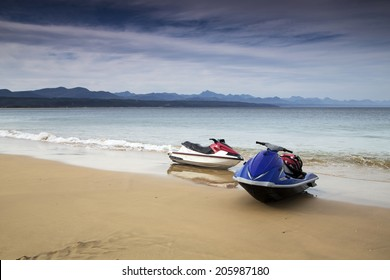 Two jet skis on the beach on an overcast day