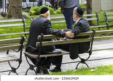 Two Jewish men wearing kippah talking in a public bench in financial district of New York