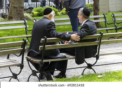 Two Jewish men wearing kippah talking in a public bench in financial district