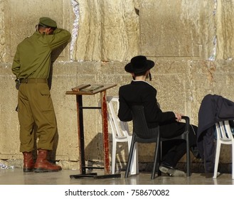 Two Jews in front of Western Wall known as Willing Wall, Israeli soldier in green uniform, stands, prays, leaning on wall, orthodox Jews, haredi, in black sits on chair and looks at soldier, table
