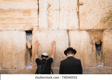 Two Jews praying at the western wall in Jerusalem