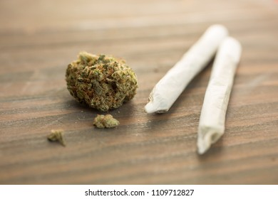 Two joints with a bud of weed on a wooden table