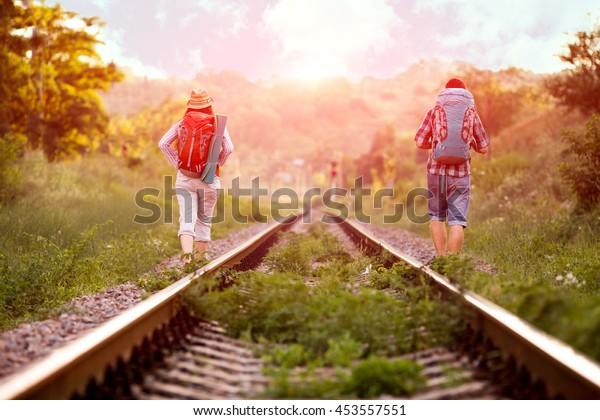 Dos jolly excursionistas hombre y mujer en ropa de viaje informal con mochilas caminando a lo largo del viejo ferrocarril rural con sol y bosque en segundo plano