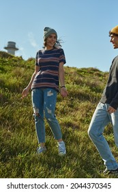 Two jovial young people talking on a steep hill and having fun