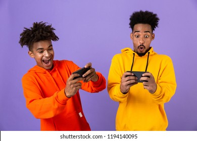 Two joyful african man friends dressed in colorful hoodies standing isolated over violet background, playing games on mobile phones