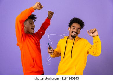 Two joyful african man friends dressed in colorful hoodies standing isolated over violet background, listening to music with earphones and mobile phone, dancing