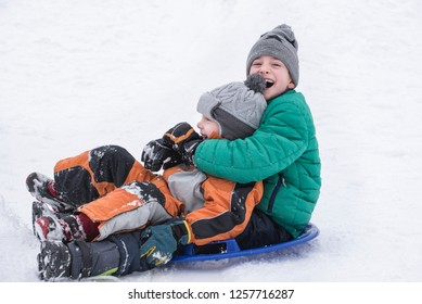 Two joyful boys slides down the hill on snow saucer. Brotherly friendship. Winter day.