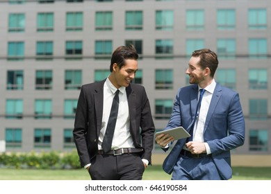 Two Joyful Business Men Using Tablet and Walking