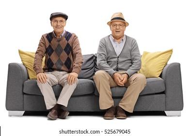 Two joyful elderly men sitting on a sofa isolated on white background