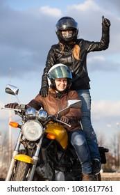 Two joyful European women driving motorcycle, girl standing behind with thumb up