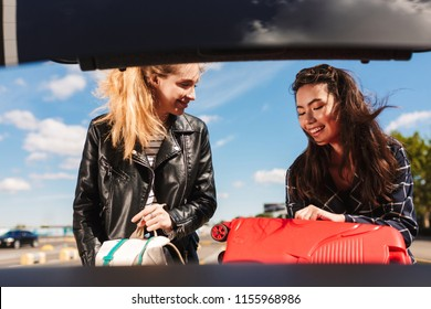 Two joyful girls happily folding suitcases into trunk of black car in  airport parking zone