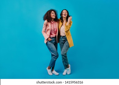 Two joyful girls posing on blue studio background. Full length photoshoot of stylish female models.