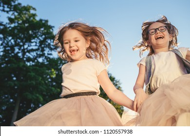 Two joyful girls running, jumping and smiling. Summer activity and leisure.