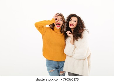 Two Joyful girls in sweaters having fun together and looking at the camera over white background