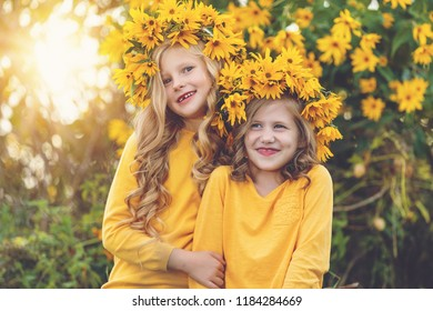 Two joyful little girls with wreaths of yellow flowers on their heads over sunset playing in the park