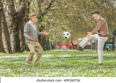 Two joyful seniors playing football in a park on a beautiful spring day