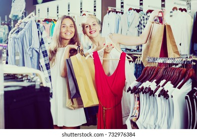 two joyful smiling girls holding clothes racks and shopping bags standing in clothes shop