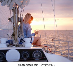 Two joyful women are celebraiting good summer day at the yacht while watching beautiful sunset.