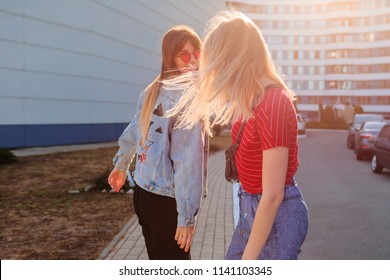 Two joyful women  having fun outdoor in sunlight. Windy hairs.  Carefree girls turns Around and laughing. Stylish jeans jacket with print. Urban background .